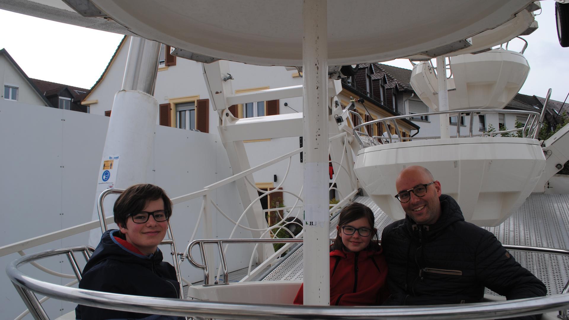 Kilian (12), Resa (10) und Benny Oehde (42) sitzen in der Gondel des Riesenrads