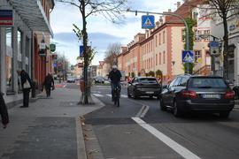 Ein Fahrradfahrer ist auf der Schlossachse in Richtung Innenstadt auf dem Fahrradstreifen unterwegs.