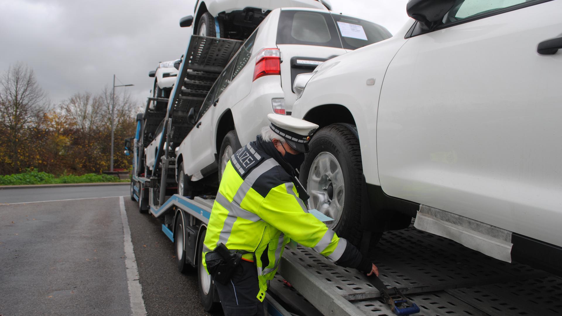 Ein Verkehrspolizist überprüft die Spanngurte eines Autotransporters.