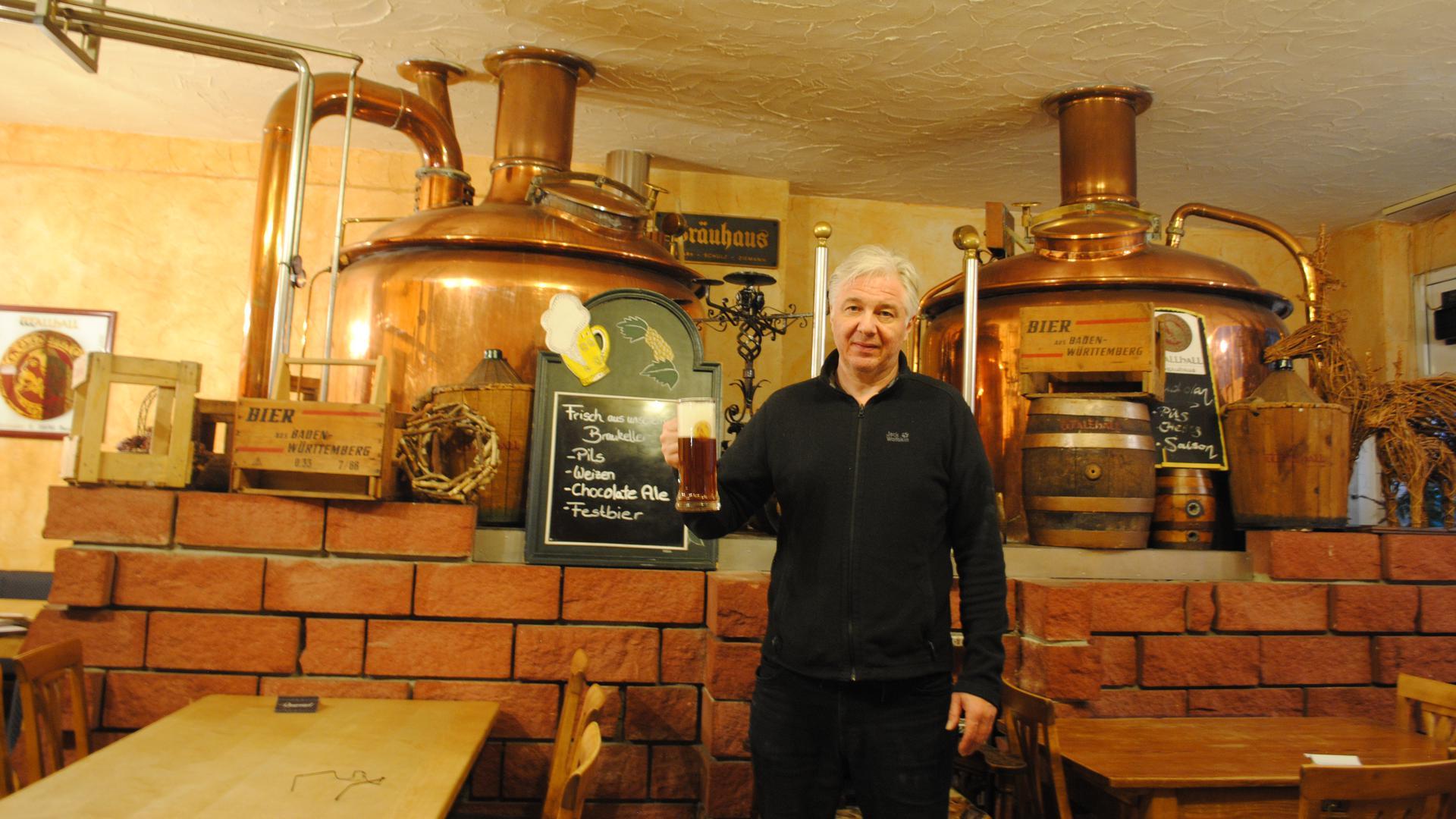 Christian Hochhaus steht mit einem Bier in der Hand vor den Bierfässern in seinem Brauhaus