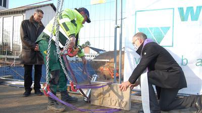 Dekan Lukas Glocker (rechts) hilft einem Bauarbeiter im Beisein von Bernhard Firnkes vom Caritasrat den Grundstein an den Kranhaken zu befestigen.