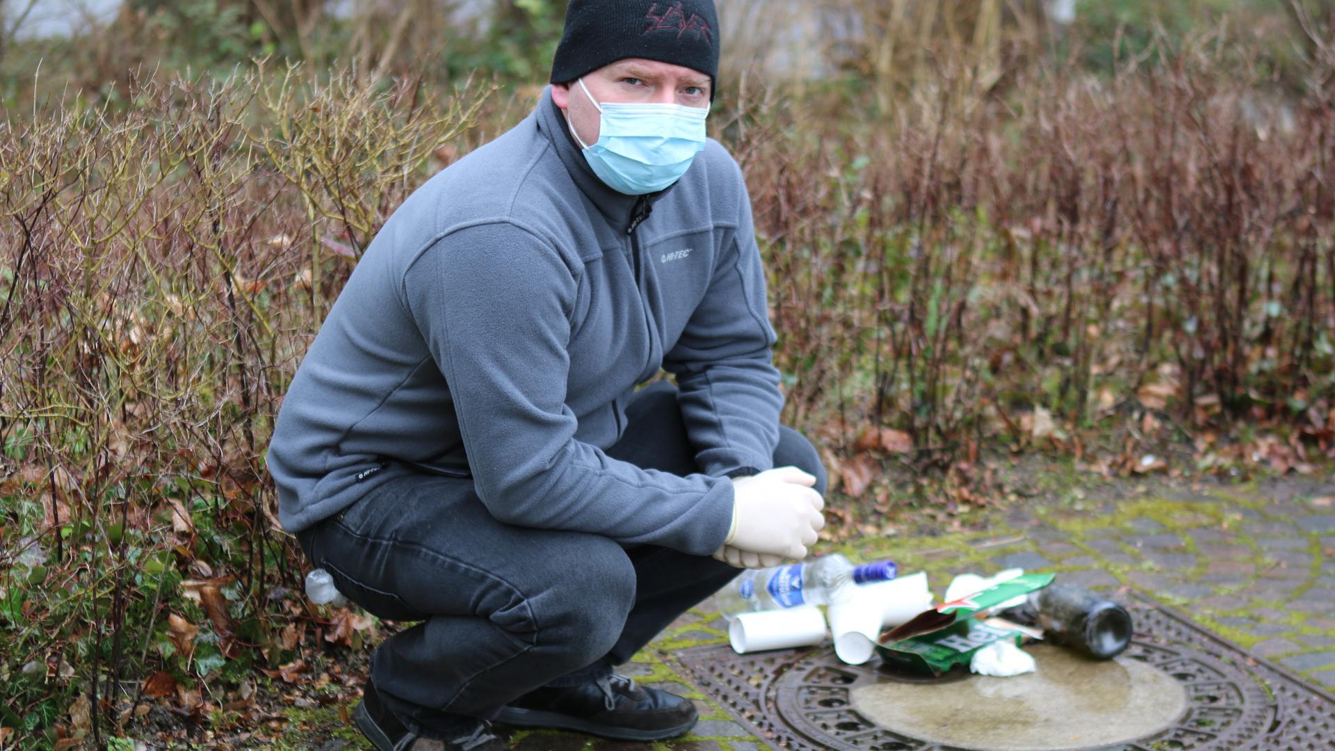 Junger Mann mit Maske vor gesammeltem Müll