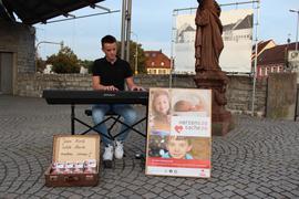 Ein junger Mann, Laurin Sigmund, sitzt in Bruchsal auf dem Fußgängerweg an seinem Piano und spielt. Davor stehen Plakate und ein Spendenkoffer für eine Hilfsaktion.