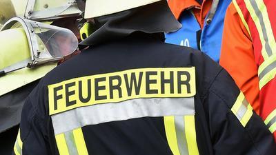 Der Schriftzug Feuerwehr steht während einer Rettungs-Übung auf der Jacke eines Feuerwehrmanns.