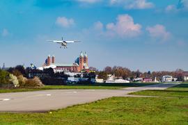 Landendes Kleinflugzeug mit Hintergrund Speyrer Dom