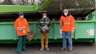 Drei Personen vor einem Altpapiercontainer