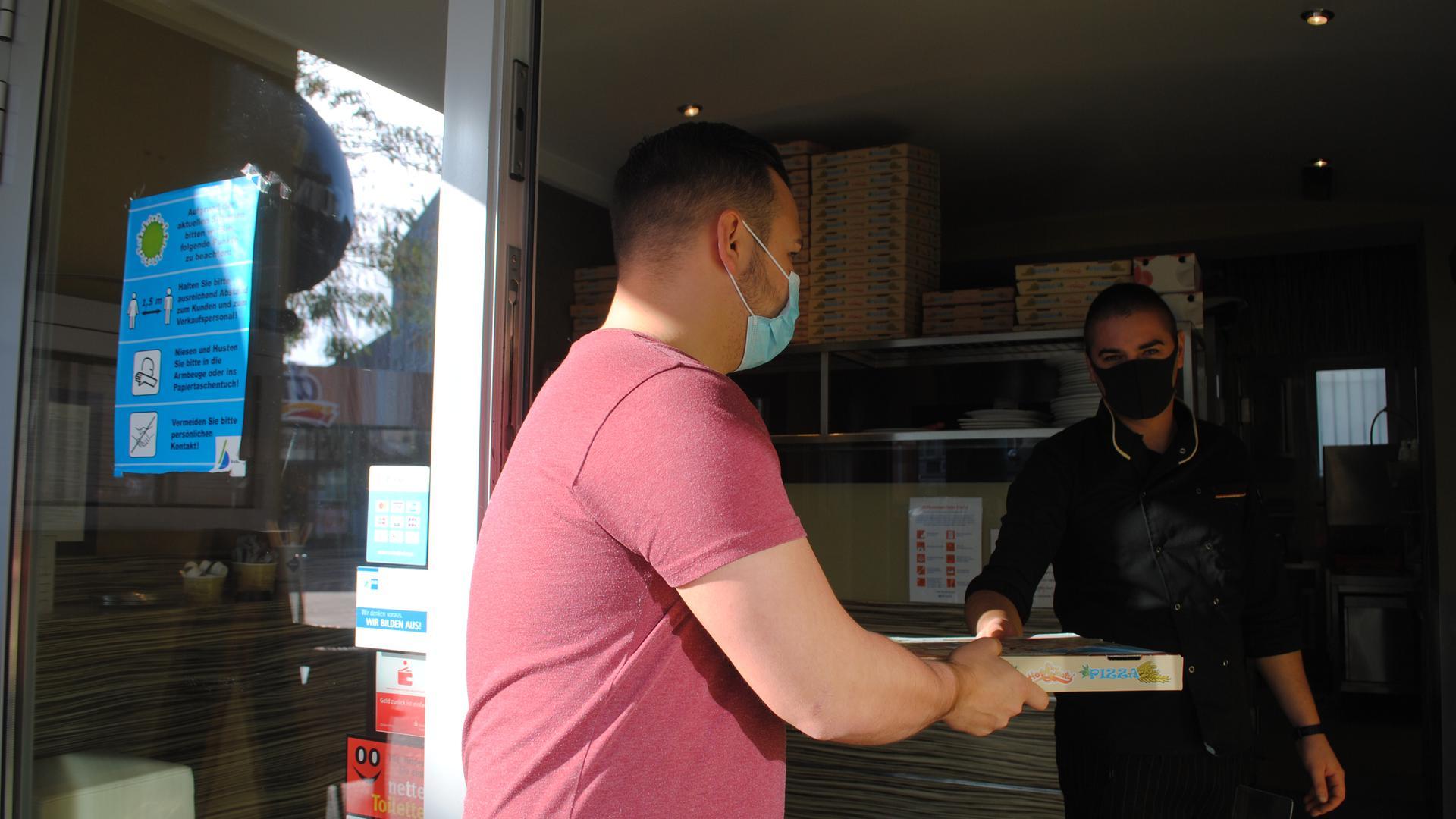 """Ein Kunde nimmt eine Pizza zum Mitnehmen beim Restaurant """"Leonardo"""" entgegen."""