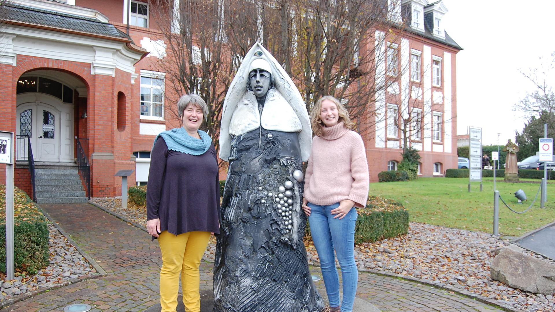 Die Hebammen Margret Bauer und Franziska Rehbein an der Skulptur Ordensschwester von Jürgen Goertz.