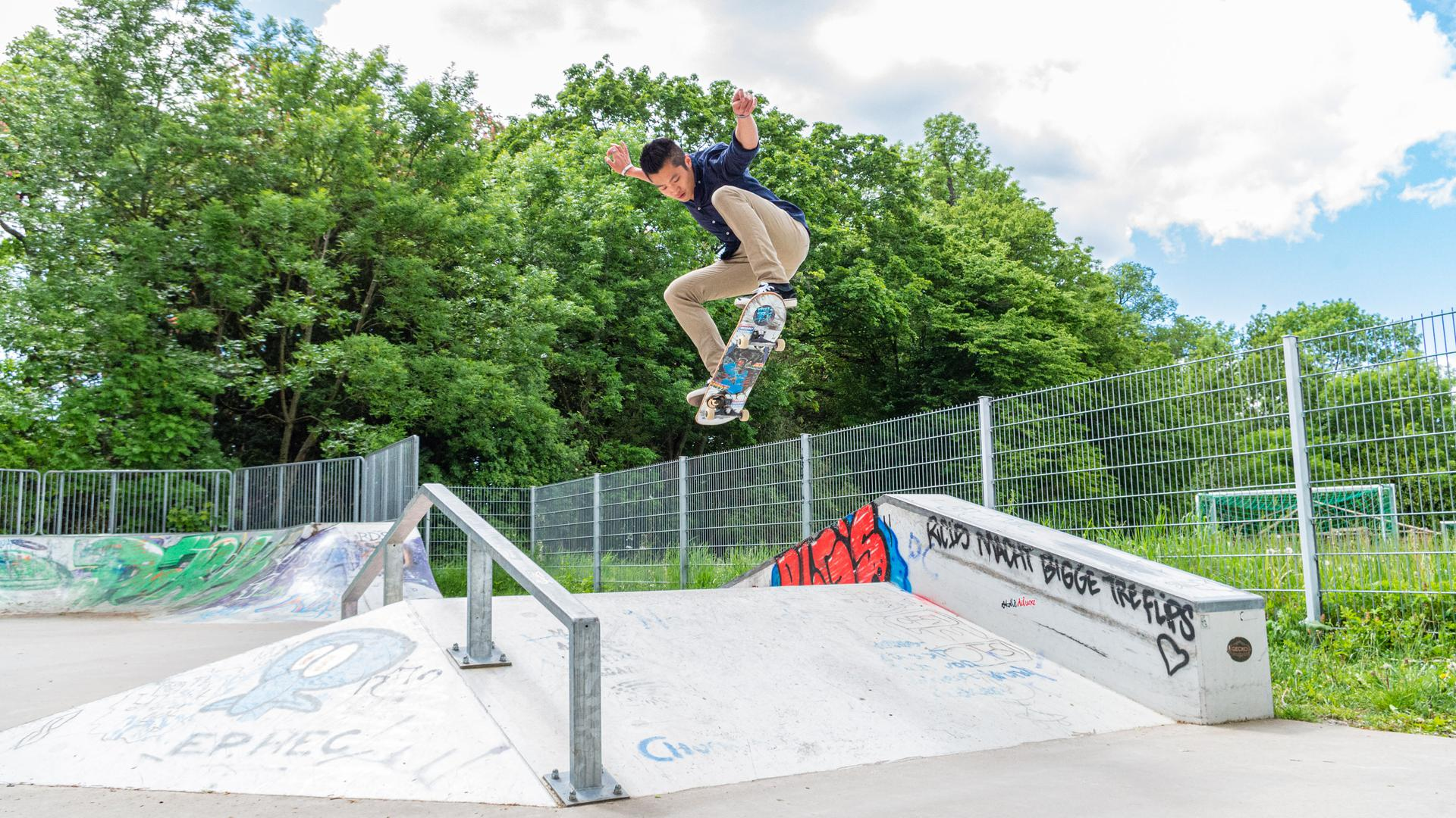 Ein junger Mann springt mit einem Skateboard über eine Rampe.