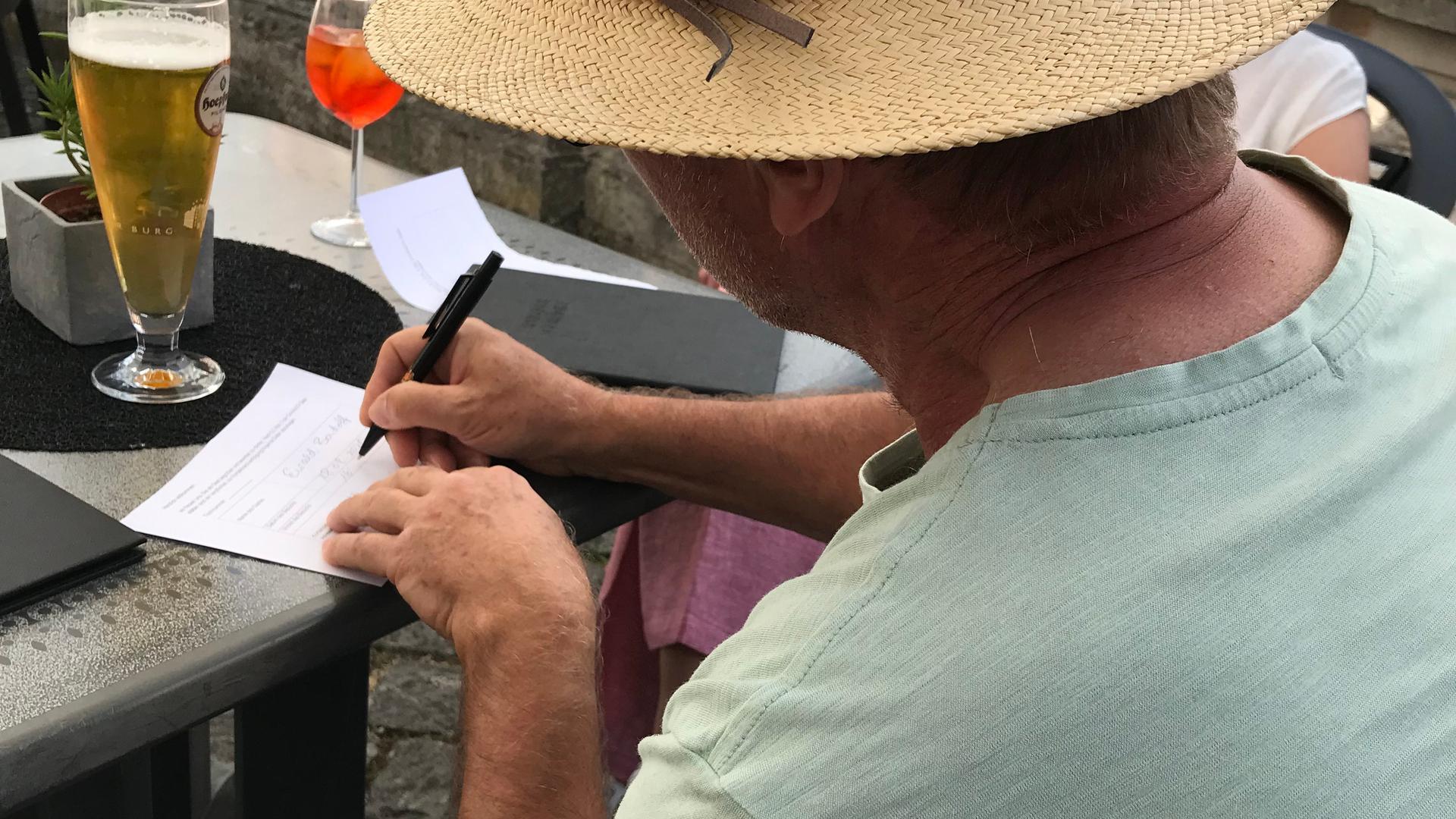 Mann mit Hut füllt Zettel aus