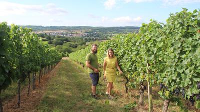 Zwei junge Leute stehen in einem Weinberg und lachen in die Kamera.