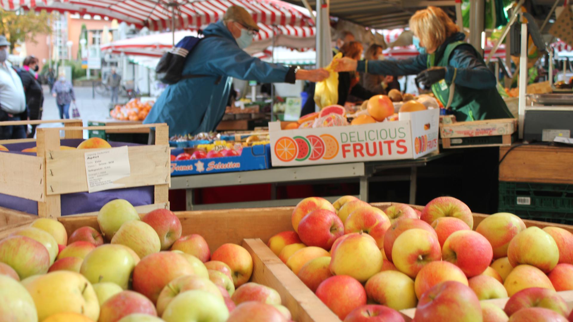 Eine Händlerin auf dem Bruchsaler Wochenmarkt reicht einem Kunden eine Tüte mit Obst und Gemüse.