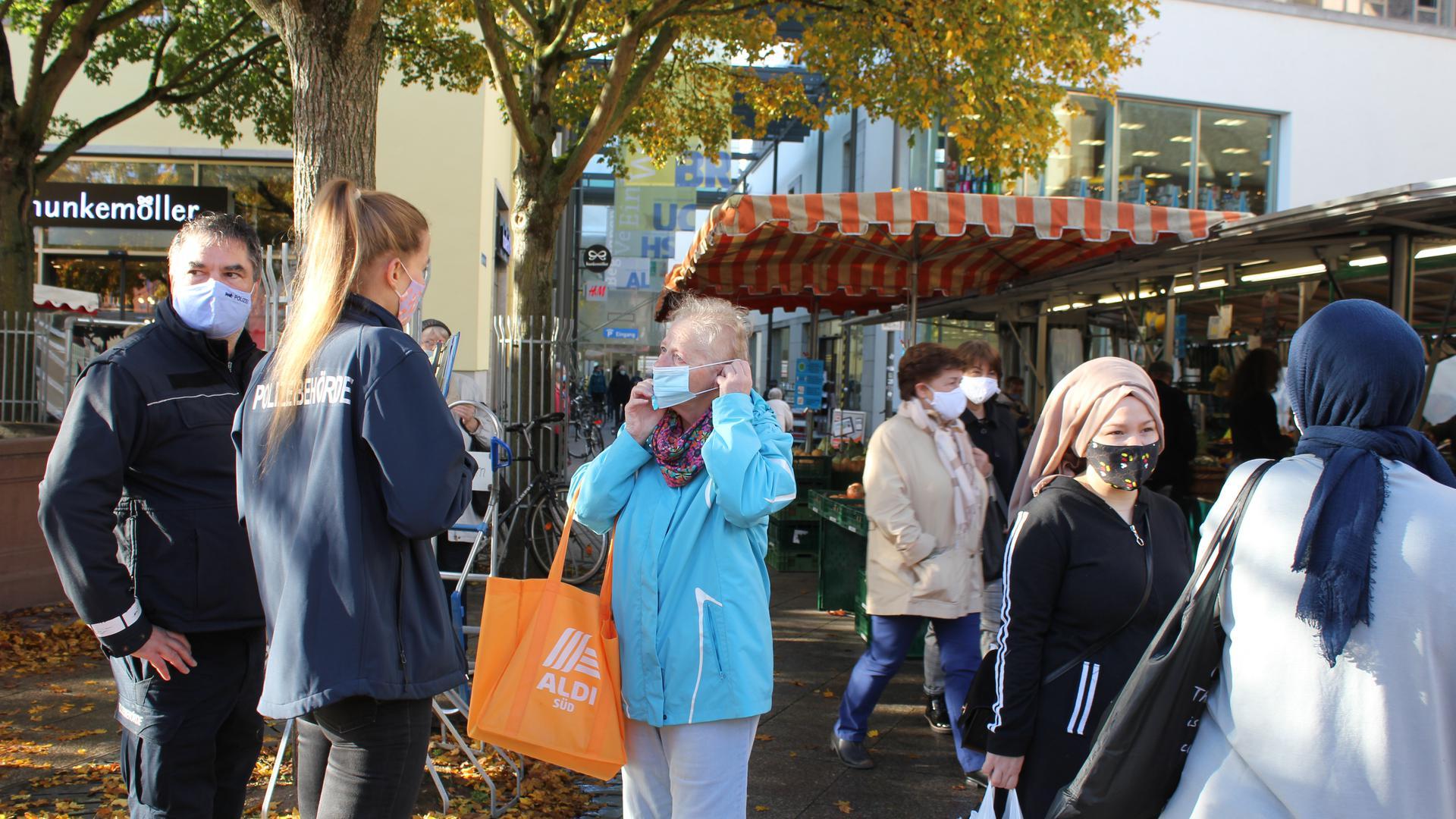 Nina Schüßler vom Ordnungsamt und Georg Völker vom Gemeindevollzugsdienst weisen eine Frau auf dem Wochenmarkt auf die Maskenpflicht hin.