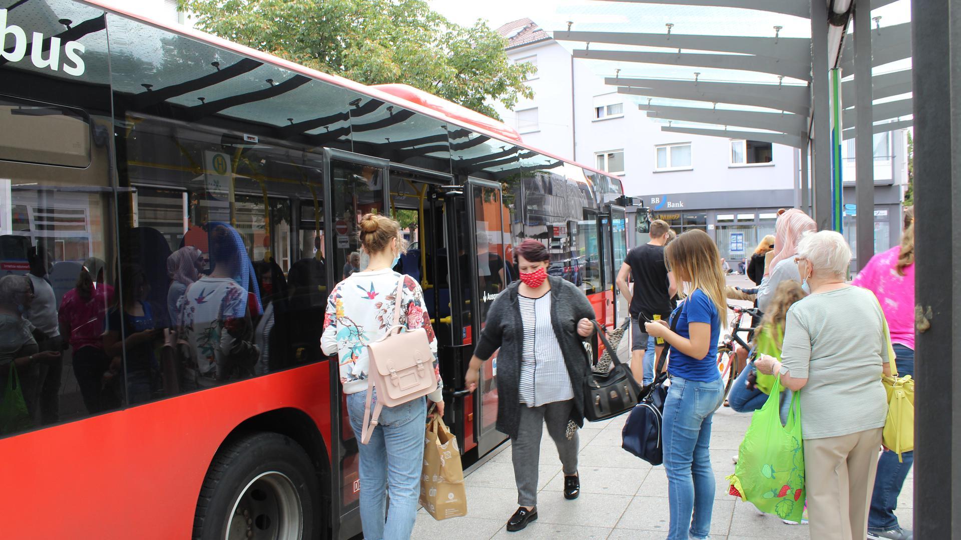 Warten auf den Bus: Die meisten Fahrgäste ziehen ihre Maske erst auf, wenn sie einsteigen.