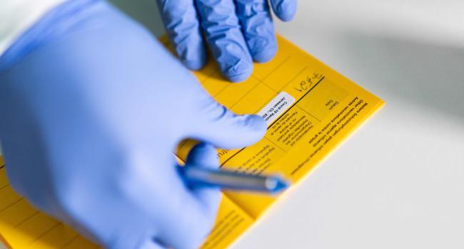 Ein Arzt füllt in einer Übergangswohneinrichtung für Geflüchtete einen Impfausweis aus. In Essen werden in sechs Übergangswohneinrichtungen für Geflüchtete mobile Impfteams eingesetzt, um die Bewohnerinnen und Bewohner mit dem Covid-19-Impfstoff von Janssen (Johnson & Johnson) zu immunisieren. +++ dpa-Bildfunk +++