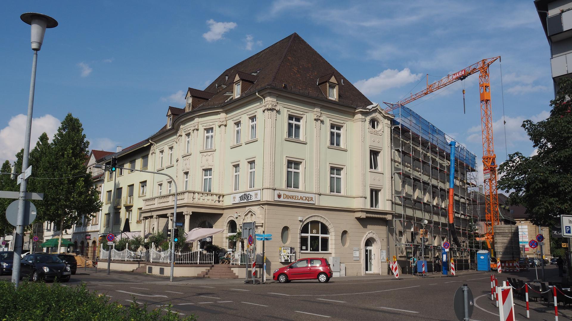 Ein Haus aus der Gründerzeit mit großer Außenwerbung an einer vielbefahrenen Kreuzung.
