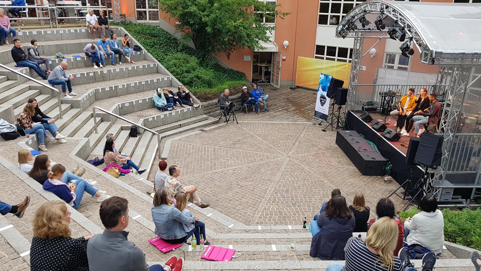 Band auf Bühnen vor Publikum im Freien.