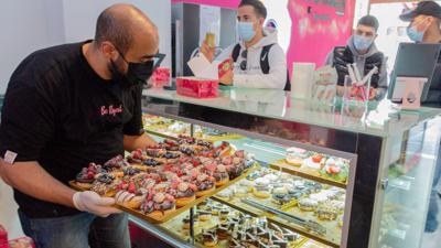 Magdi Safadi stellt eine Platte mit Donuts in seine Auslage im Donut-Laden in Bruchsal.