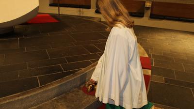 weibliche Ministrantin mit grünem Unterrock kniet vor dem Altar und hat die Glöckchen vor sich