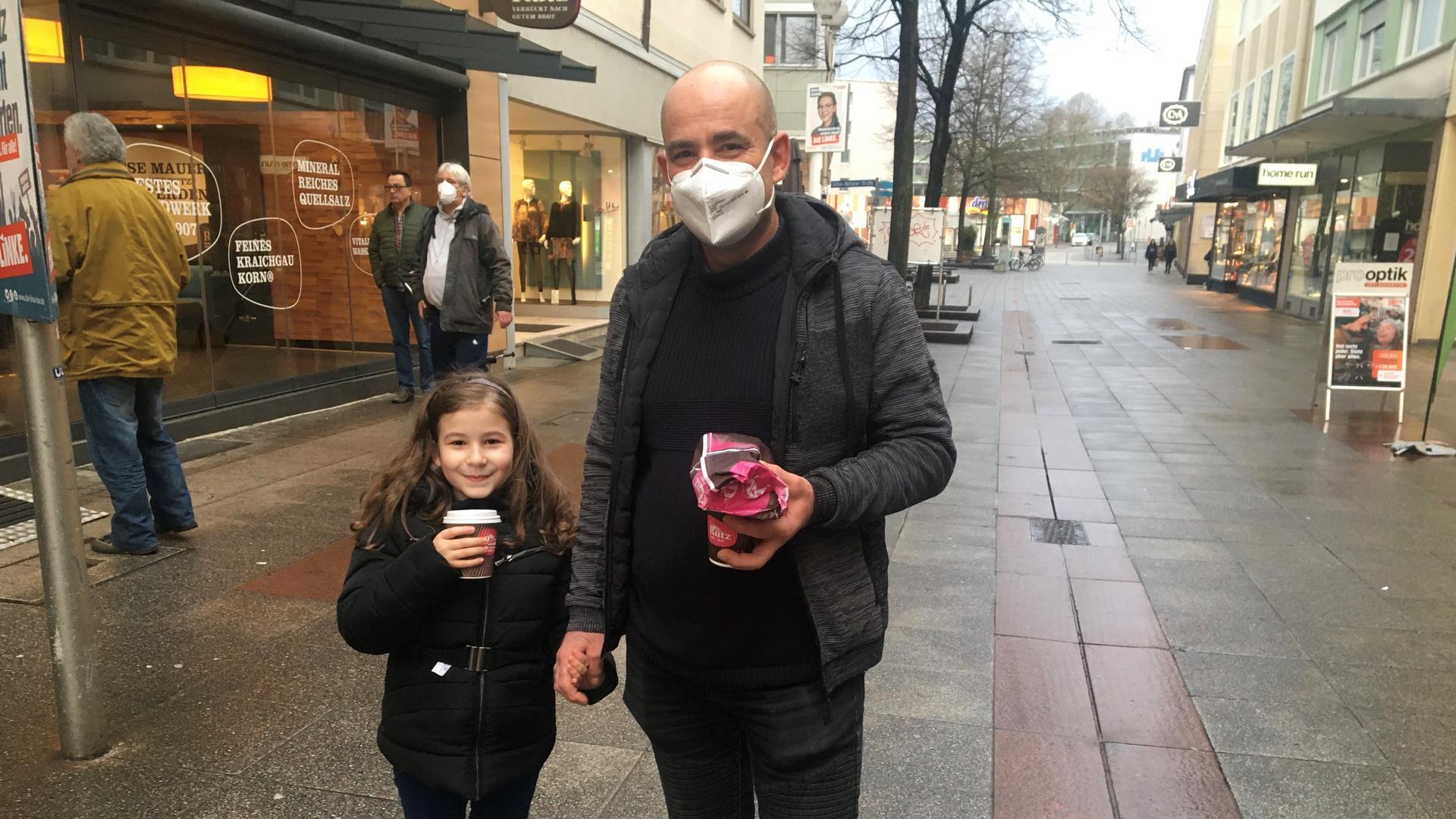 Mann mit Kind und Backertüten