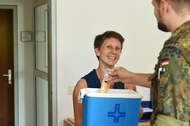 Pastoralreferentin Monika Hansmann verteilt bei heißen Temperaturen Eis in der Nibelungen-Kaserne an einen Soldaten in Walldürn.