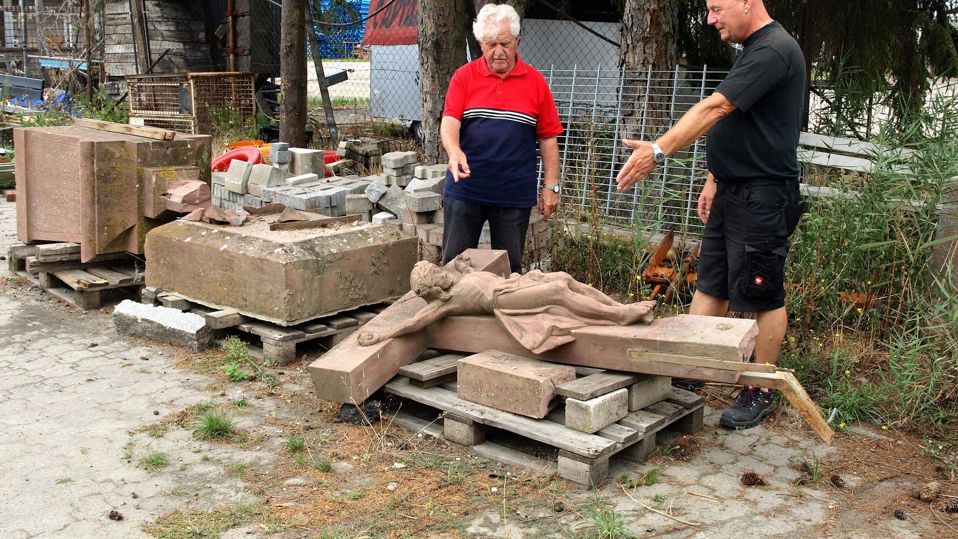Im Bauhof aufbewahrt: Heimatvereinsvorsitzender Heinz Kraus (links) und Bauhofmitarbeiter Uwe Kammerer betrachten das beschädigte Steinkreuz