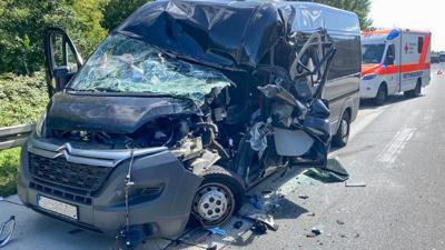 Total zerstörter Kleintransporter, dahinter ein Rettungswagen und ein Warndreieck.