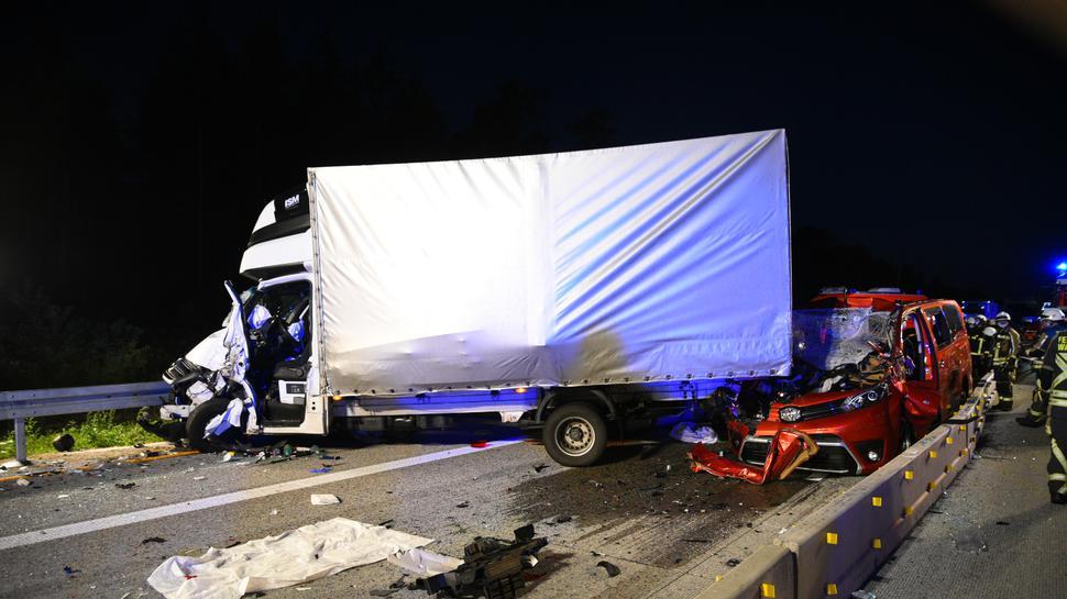Ein weißer Lastwagen steht quer auf der Fahrbahn. Unter dem Heck ist ein rotes Auto eingeklemmt.