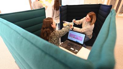 """Anja Gill und Diana Popa (r), Mitarbeiterinnen des Karlsruher Drogerieunternehmens dm, arbeiten in der Firmenzentrale, die """"Dialogicum"""" genannt wird, in Besprechungssofas. Die am 28.01.2020 beginnende Bildungsmesse Learntec befasst sich in diesem Jahr auch mit dem Vormarsch von """"New Work"""". Unternehmen verstehen darunter, ihren Mitarbeitern in der digitalen Welt veränderte räumliche, technische und zeitliche Rahmenbedingungen anzubieten. dm hat so ein offenes Konzept räumlich umsetzt. +++ dpa-Bildfunk +++"""