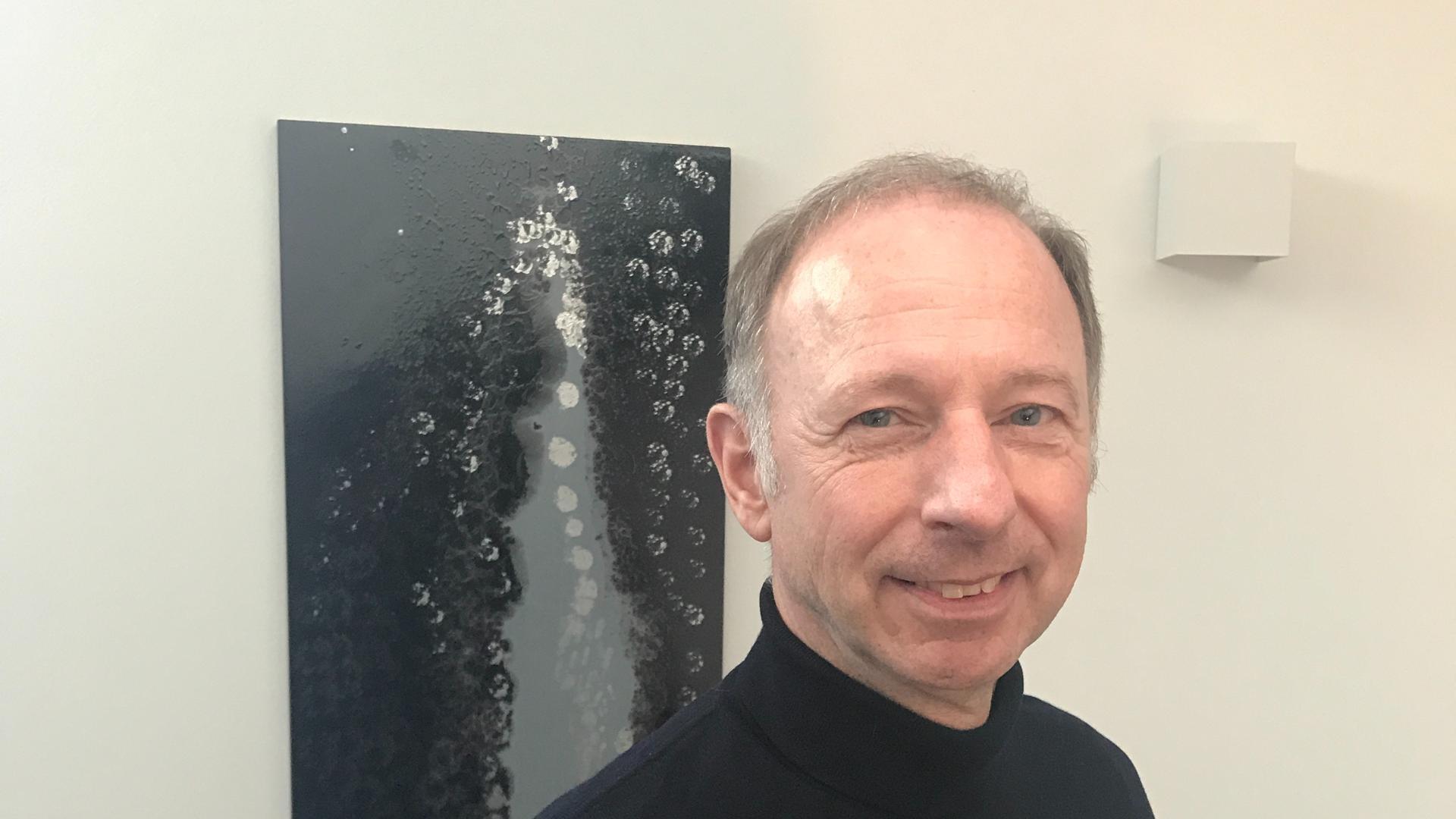 Mann vor schwarz-weißem Gemälde.