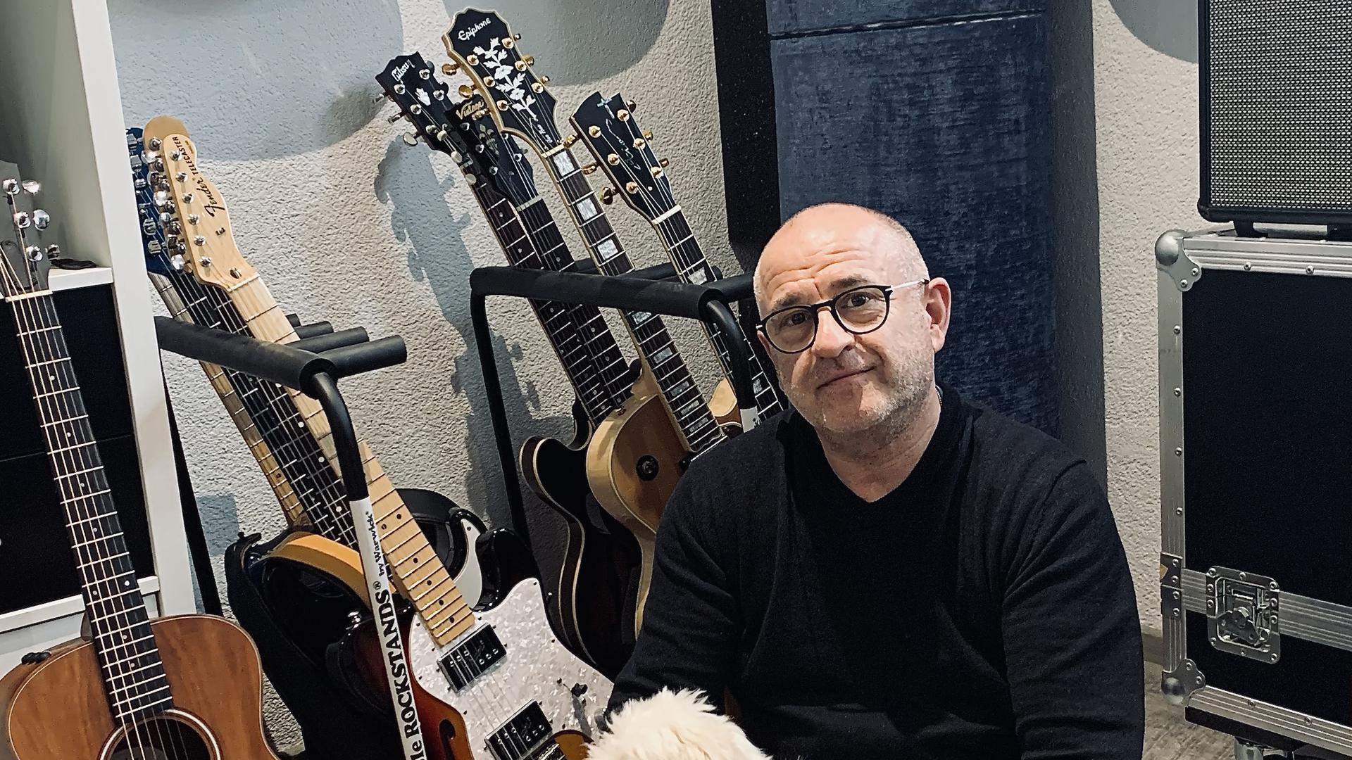 Musiker Freddy Sicko mit seiner Gitarrensammlung und seinen Hunden