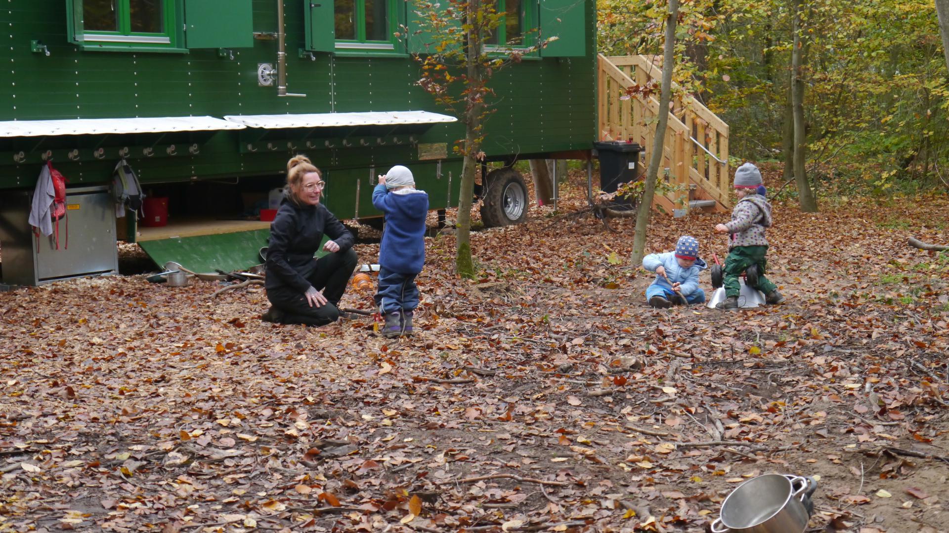 Spielende Kinder mit Leiterin