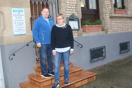Ehepaar vor einem Haus mit vergitterter Tür