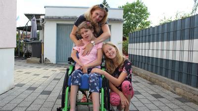 Mädchen im Rollstuhl zusammen mit Mutter und Schwester