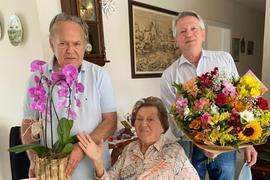 Zwei Männer gratulieren einer Frau
