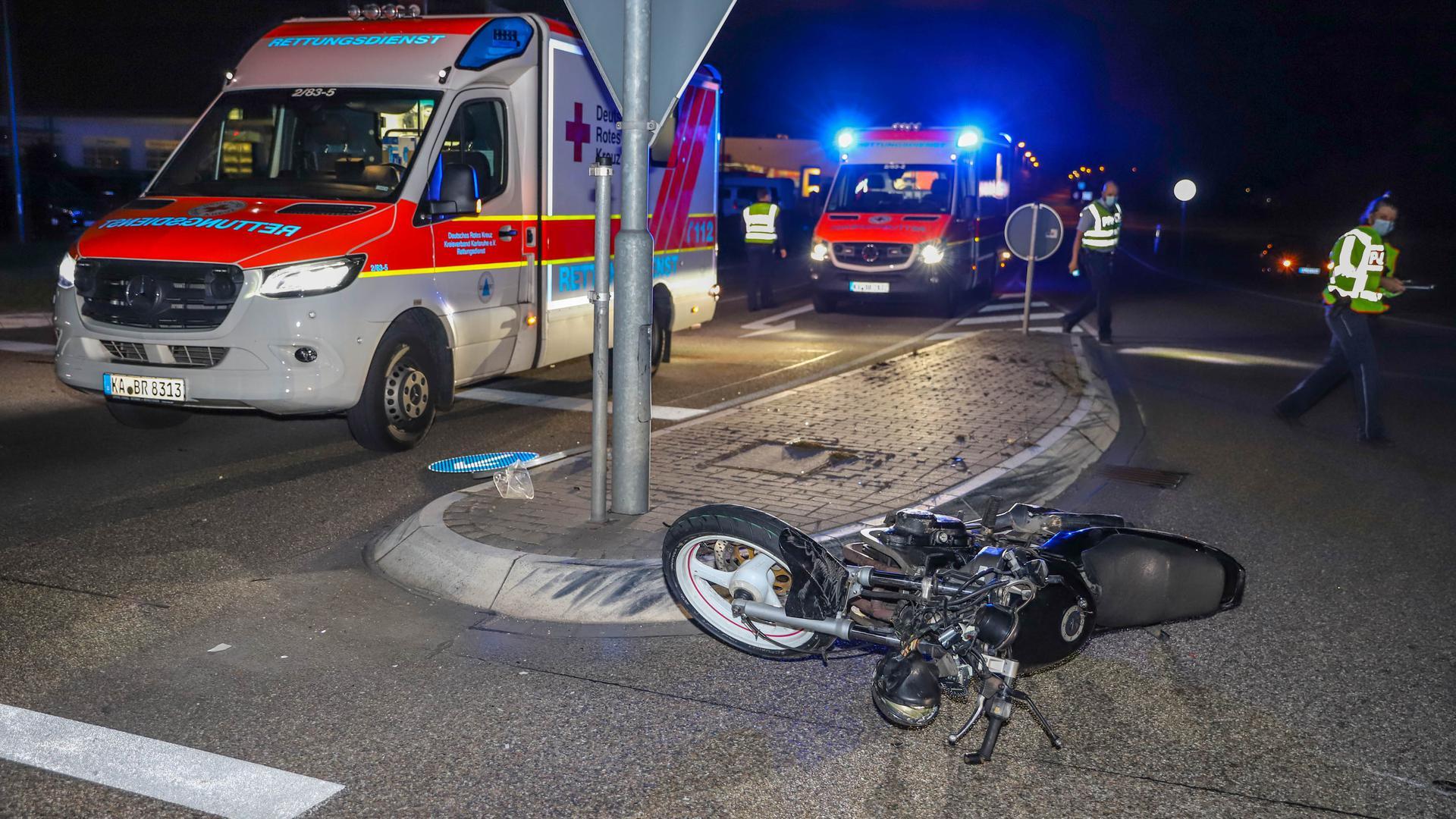 Ein schwarzes Motorrad liegt auf der Fahrbahn. Im Hintergrund zwei Krankenwagen mit Blaulicht.