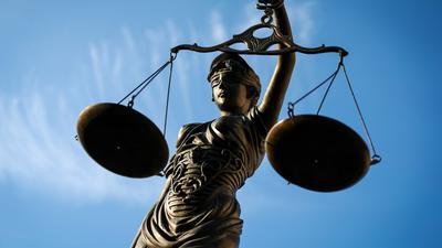 Eine Statue der Justitia hält eine Waage in der Hand.