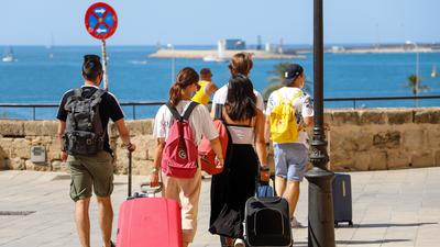 Touristen gehen mit ihren Rollkoffern durch die Stadt.