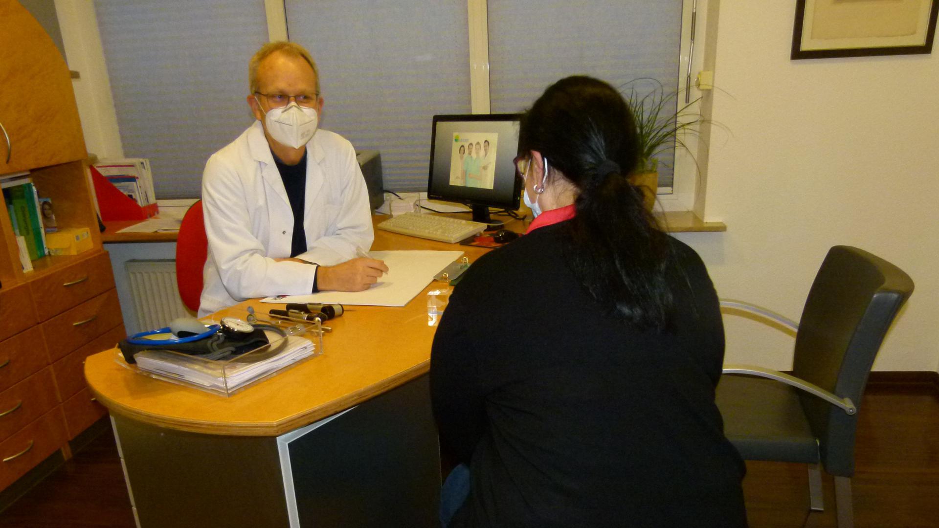 Mediziner berät mit Mundschutz eine Patientin