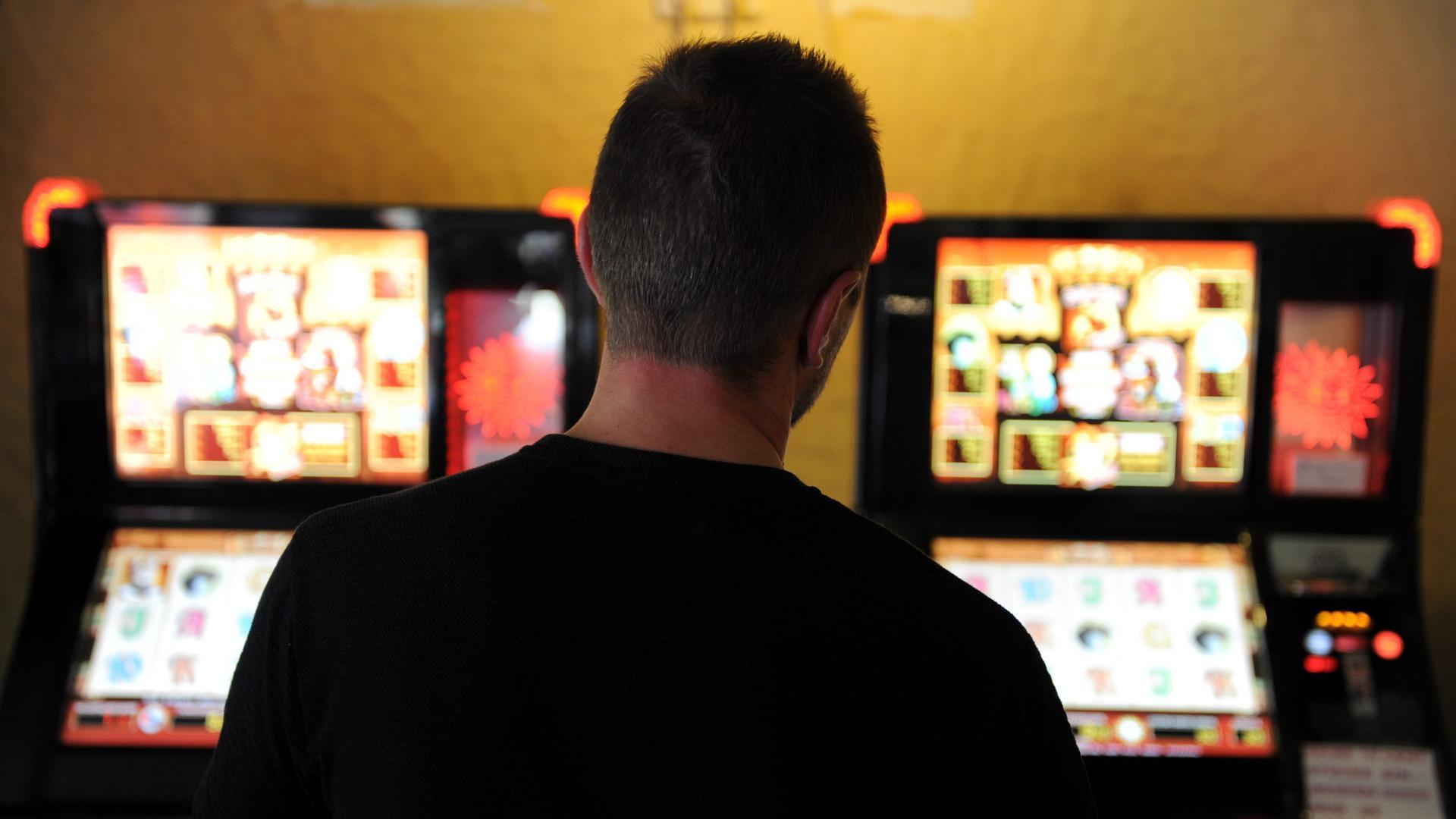 Ein Mann steht vor zwei Glücksspielautomaten