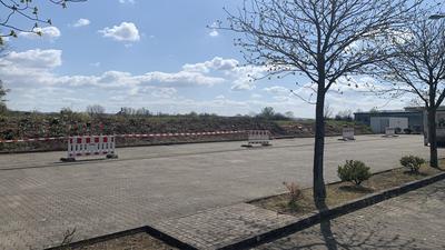 Freies Feld und gepflasterter Bereich mit Bäumen