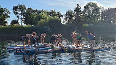 Frauen machen Yoga auf dem See