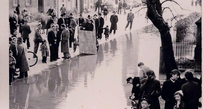 Altes schwarz-weiß Foto mit Menschen am Hochwasser.