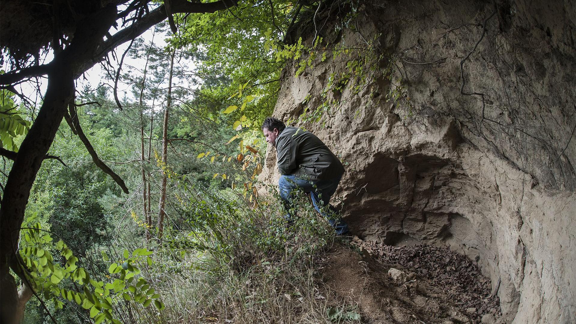 """Hier sitzt Robert Wormer an einem Odenheimer Lärmenloch. Früher war es eine ganz geschlossene Erdhöhle. Doch an der Kante eines Steinbruchs im Zinkenbusch wurde das Kulturdenkmal """"aufgerissen""""."""
