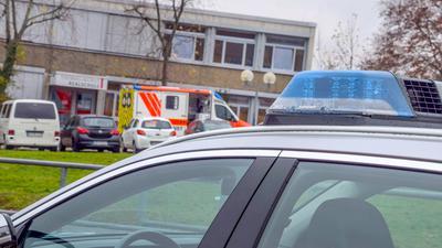 Einsatzfahrzeuge stehen vor einer Realschule.