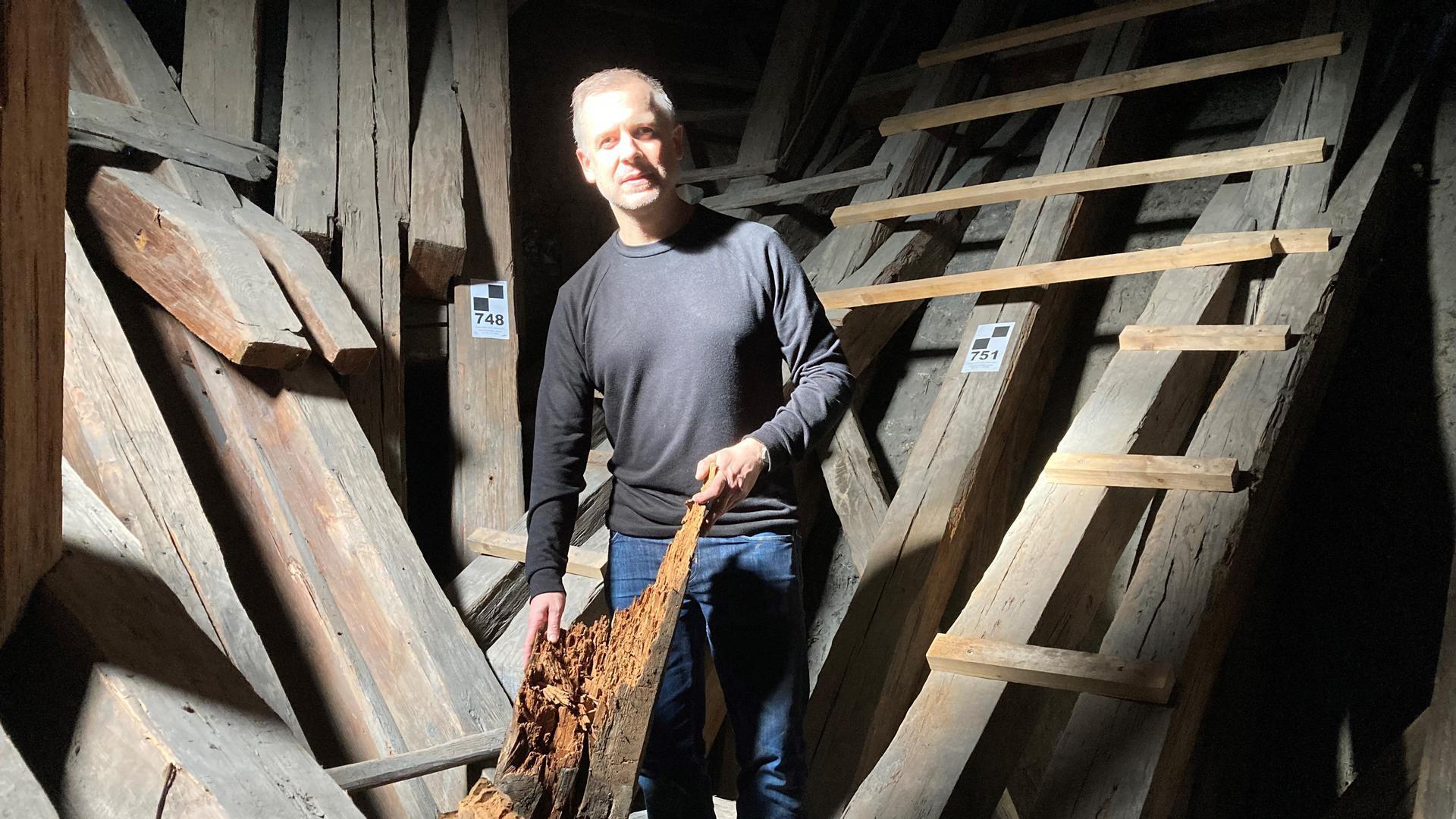Da ist nicht der Wurm, sondern der Hausschwamm drin: Architekt Daniel Henecka zeigt im Dachgestühl der Bruchsaler Peterskirche die schadhaften Balken.