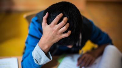 Ein Junge sitzt grübelnd an seinen Schularbeiten. +++ dpa-Bildfunk +++