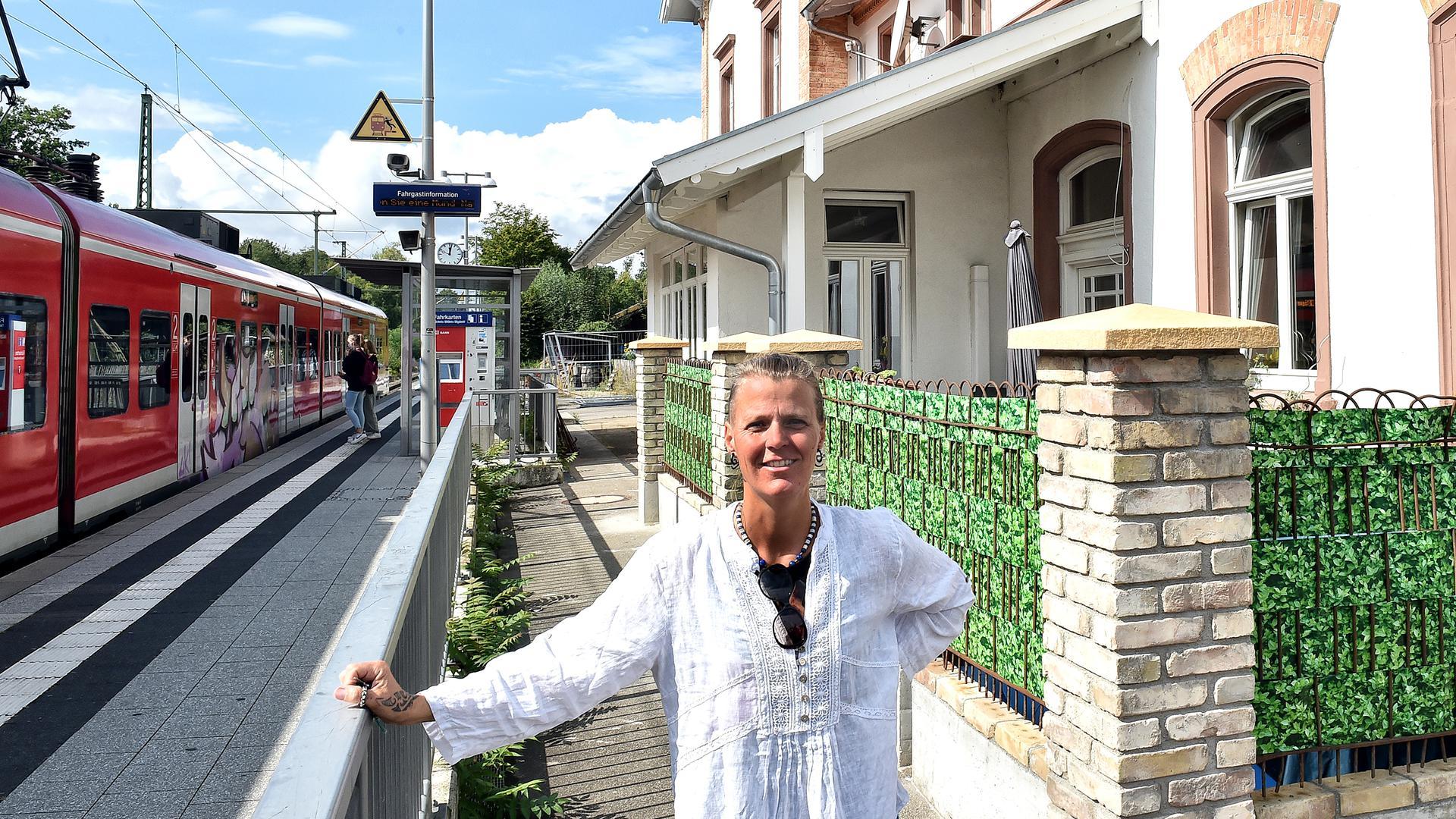 Randi Michels steht vor ihrem Bahnhofsgebäude in Rheinsheim. Im Hintergrund steigen Menschen in einen roten Zug ein.