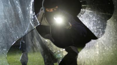 gestelltes Foto: nächtlicher Einbrecher blickt durch zerschlagene Fensterscheibe