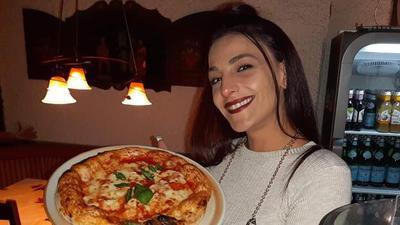 Junge Dame mit toller Pizza auf einem Teller in der Hand